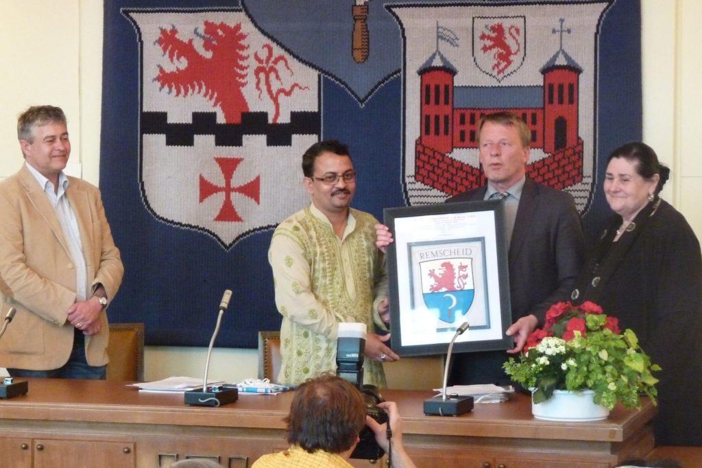 Dr. Lenin dankt dem Oberbürgermeister, Herrn Mast-Weisz, mit einem Logo der Stadt, gewebt von Webern des PVCHR aus Varanasi.